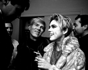 Teatime on Mars: black-and-white photograph of Andy Warhol and Edie Sedgwick laughing and talking to people.