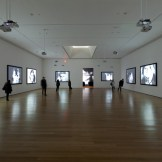 Installation view of Andy Warhol: Motion Pictures at The Museum of Modern Art, 2010. Left to right, Screen Test: Susan Sontag (1964), Screen Test: Dennis Hopper (1964), Screen Test: Kathe Dees (1964), Screen Test: Edie Sedgwick (1965), Kiss (1963–64), Screen Test: Lou Reed (1966), Screen Test: Kyoko Kishida (1964), Screen Test: Baby Jane Holzer (1964), and Screen Test: Donyale Luna (1964).