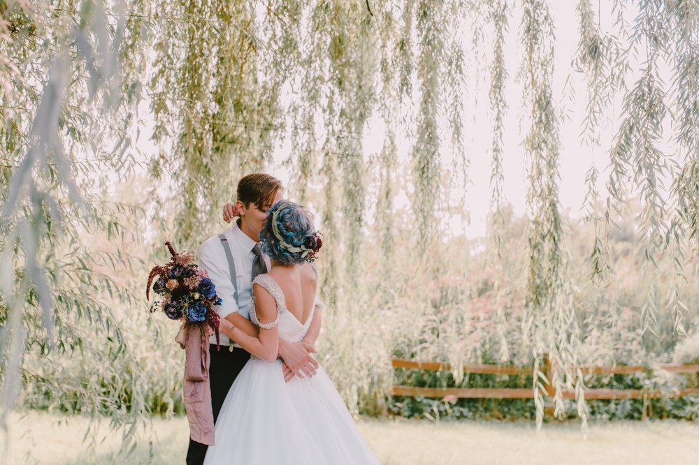 Light-skinned bride and groom kissing under a willow tree in the sun.