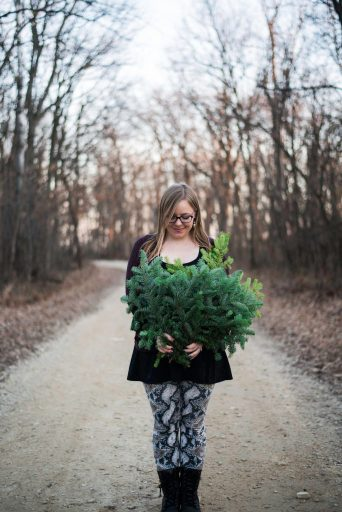 White woman holding evergreen branches in the middle of a dirt road in the winter.