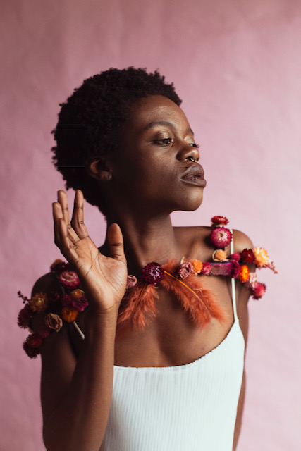 Dark-skinned woman with short black hair wearing a capelet of dried flowers in fall colors.