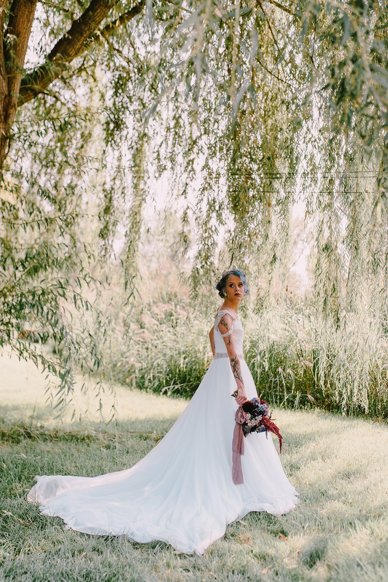 White woman in wedding gown under a willow tree in summertime, holding a dark bouquet of flowers.