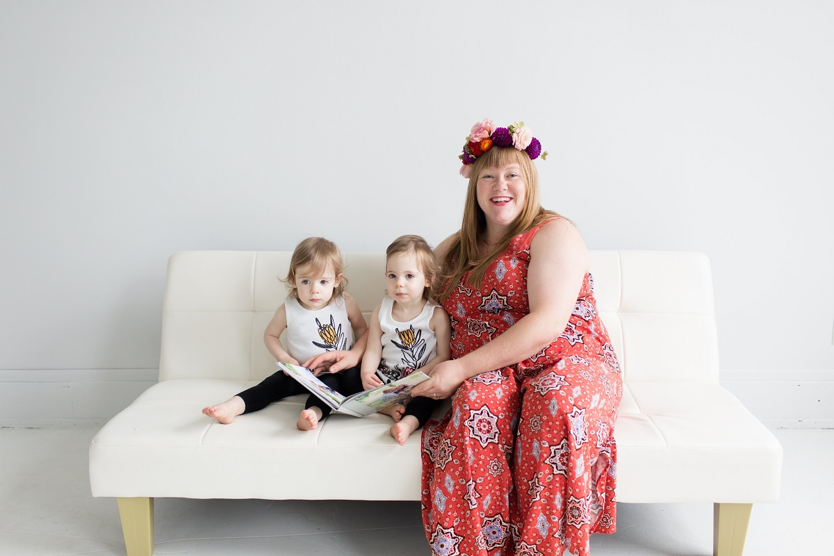 White woman in red summer dress and floral crown reading a book to twin toddlers.