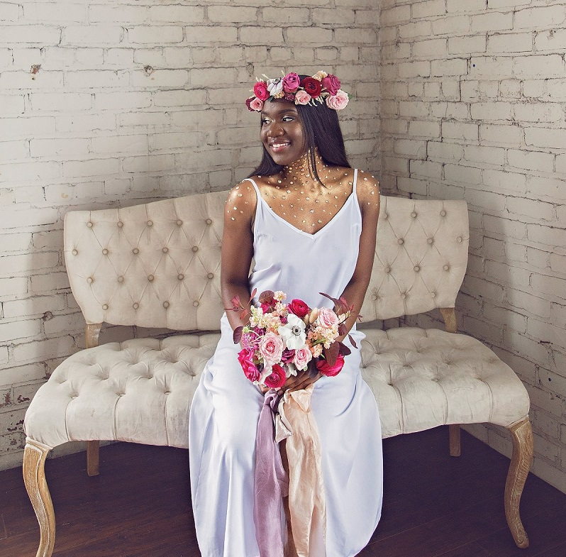 Dark-skinned woman with long, black hair sitting on a white couch with a pink and white floral bouquet and bridal crown.