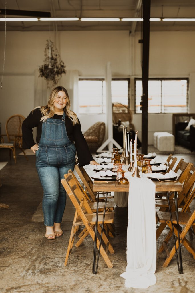 Meghan Buck, owner of buck & rose wedding planning in Minneapolis stands in front of a styled table decorated for a wedding.