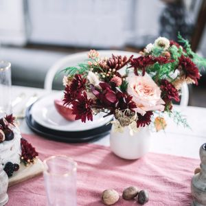 Flower arrangement on a holiday table with candles, pink linen and cake decorated with fruit and flowers. Minneapolis Florist