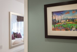 The McDonald Residence double bedroom from hall showing modern artwork of Edinburgh's Old Town