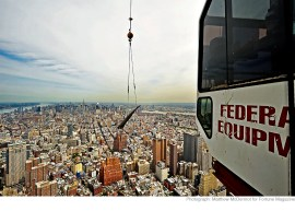 A slide crane attached to the north face of 1 World Trade Center carries steel reinforcement bars (rebar) about 1,200 feet above Manhattan