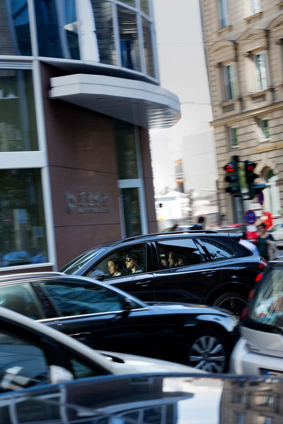 Ein Auto fährt durch das Frankfurter Bankenviertel. Im Fahrzeug sitzen ein Mann am Steuer, eine Frau auf dem Beifahrersitz und ein Mädchen auf dem Rücksitz. Alle drei sind im Schein der Sonne gut zu sehen, die wie ein Scheinwerfer ausschließlich ihre Gesichter beleuchtet; der Rest des Auto-Inneren liegt im Dunkeln.