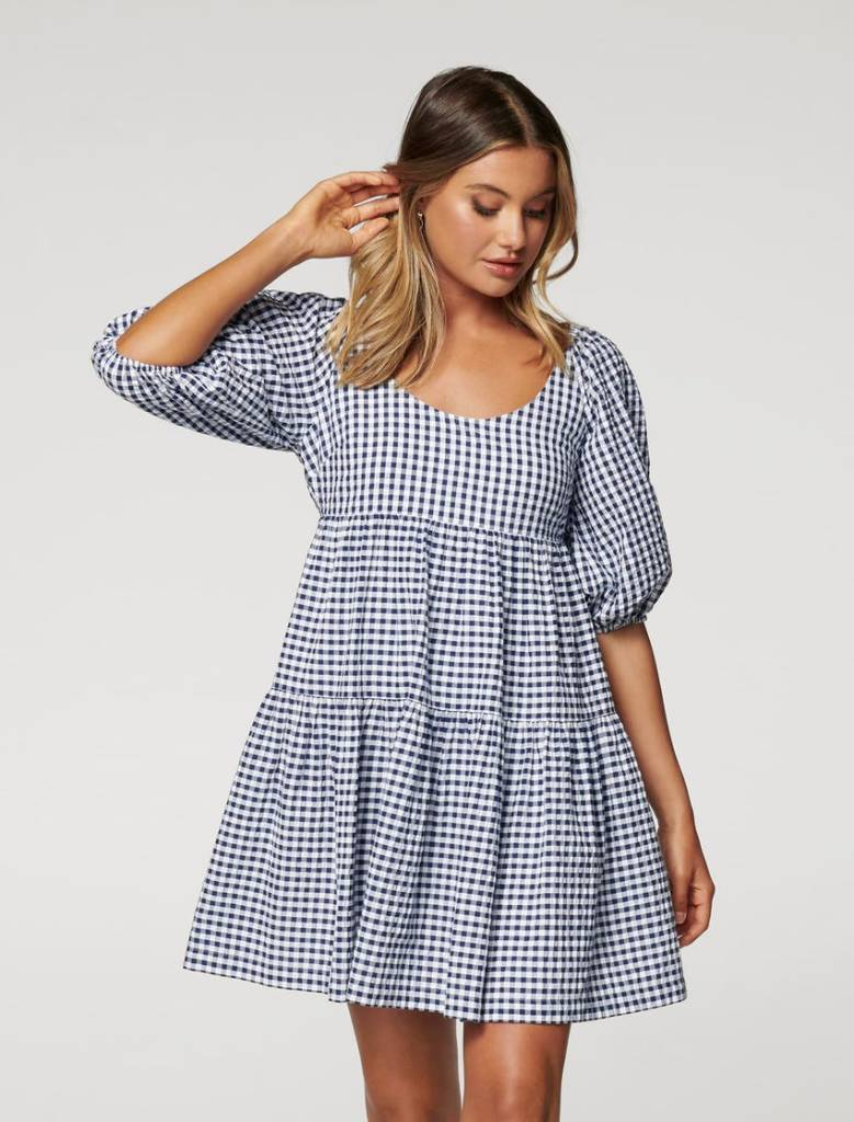 girl wearing gingham empire waist babydoll dress from Ever New