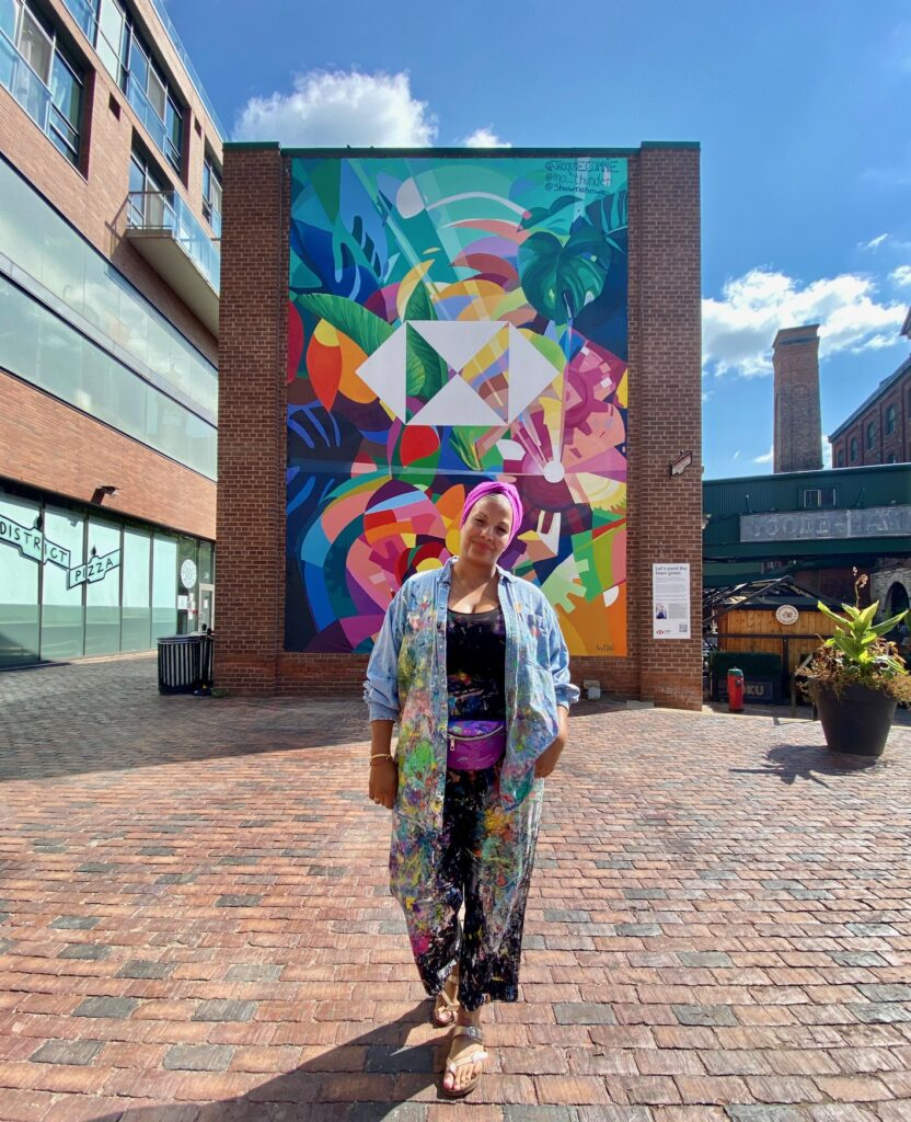 artist Jacquie Comrie in front of artwork available throughout September