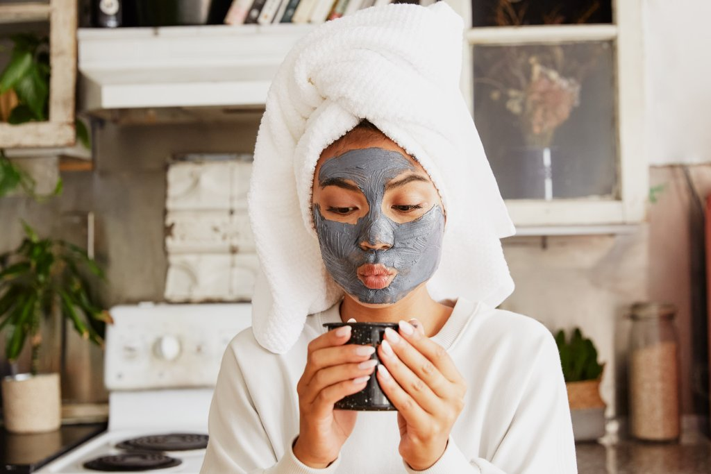 girl with face mask drinking tea during evening routine