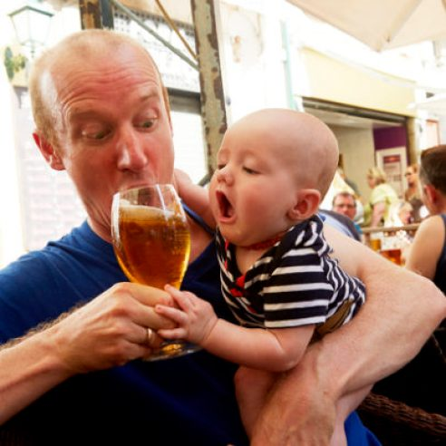 Baby trying to drink beer