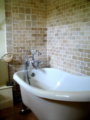 A pretty slipper bath in the Apricot bedrooms en suite backed by Travertine tiles