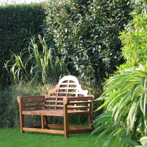 Lutyens style bench surrounded by lush planting at Ednovean Farm