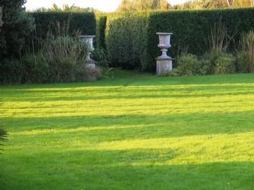 lush green lawn to Italian gardne entrance framed by urns