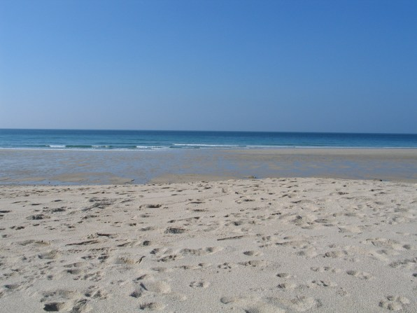 silvery white Sand blue seas and sky