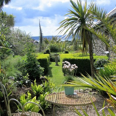 View over a formal garden to the sea from a bedroom at Ednovean Farm