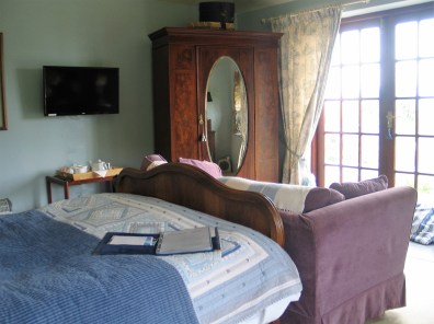 The light airy blue bedroom with a TV and hospitality tray