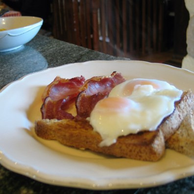 Poached eggs on toast with gilled bacon on a vintage french style plate