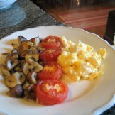 A vegetarian option fro breakfast of tomatoes, mushrooms and scrambled eggs