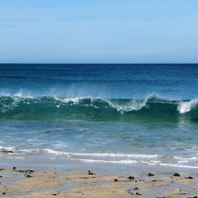 Perfect blue seas and a wave breaking on the shore in Cornwall