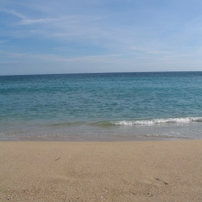 Crystal clear seas lapping the beach at Porthcurno