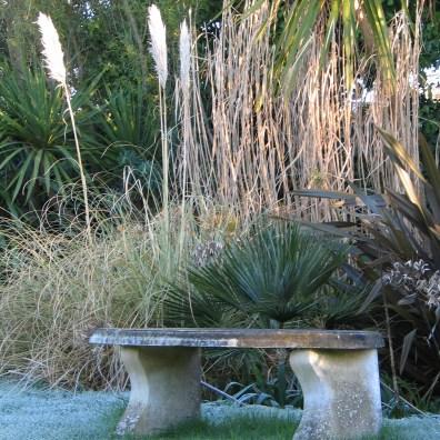 a stone garden bench in a rare frost