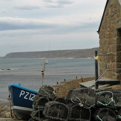 lobster pots with the cornish cliffs across the aby