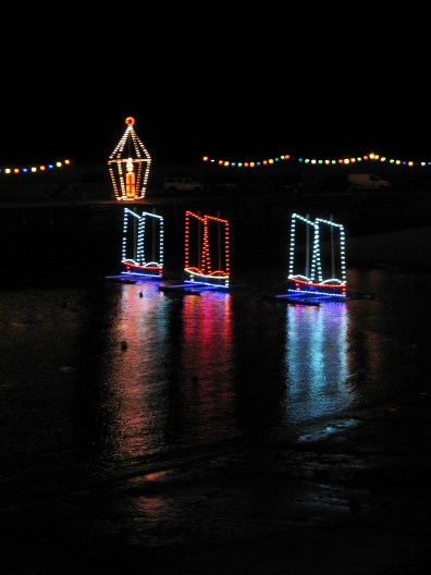Three ships in christmas lights on the sea