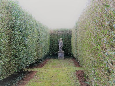 formal garden aisle leading to statue