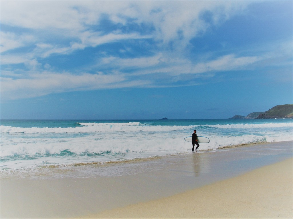 A surfer emerging from the waves at Sennen