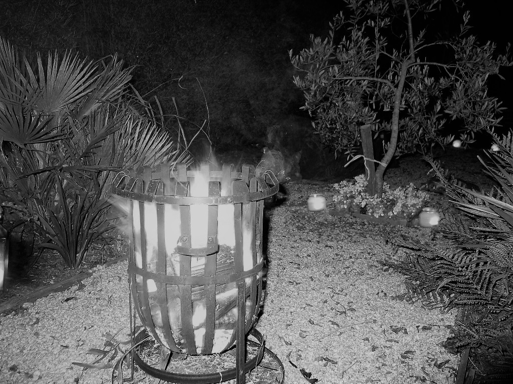 Flaming brazier in a candle lit garden