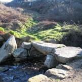 Ancient bride across stream on coastal footpath