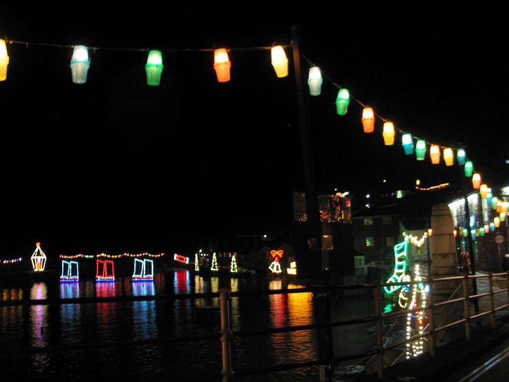 Brightly coloured lanterns sail above the harbour road at Mousehole