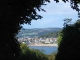 Coastal town glimpsed through trees Marazion