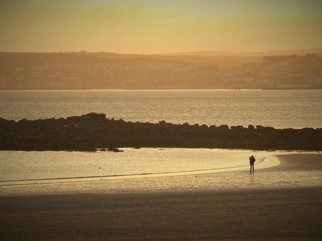 Photographer on an empty beach at sunset