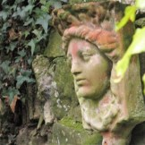 Old terracotta head mounted on wall