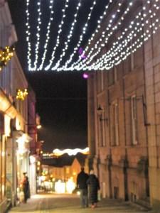 couple walking hand in hand under nostalgic Christmas lights of Penzance