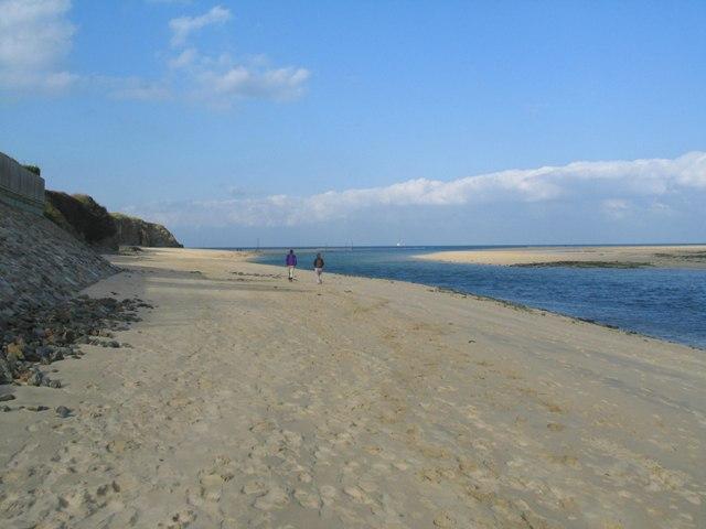 couple walking beside blue sea