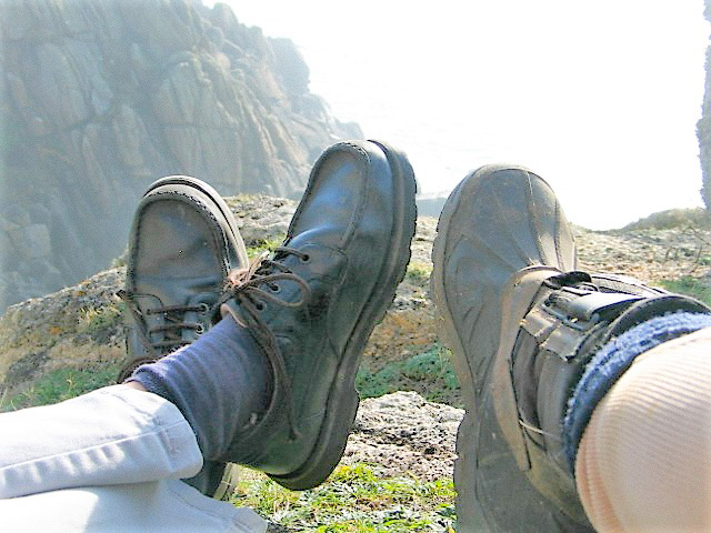 Two sets of feet lounging on cliff