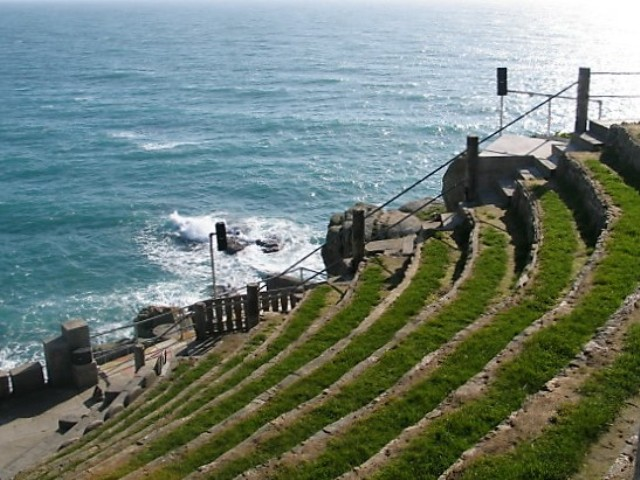 Grass seats rise in tiers from the Minack theatre stage