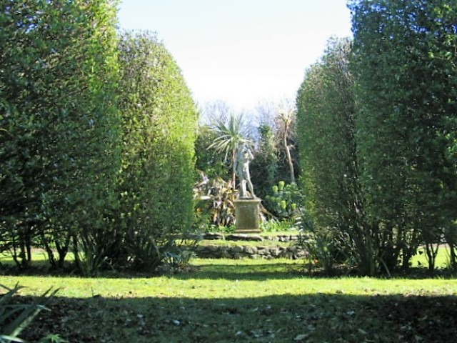 Formal hedges framing statue