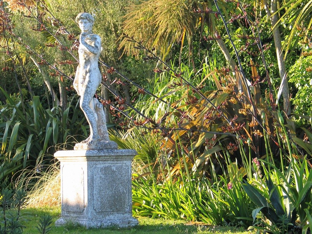 formal statue in the golden hour of a summer garden