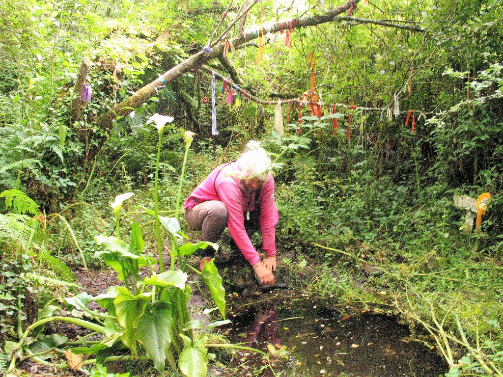 Woman crouching beside madron holy well