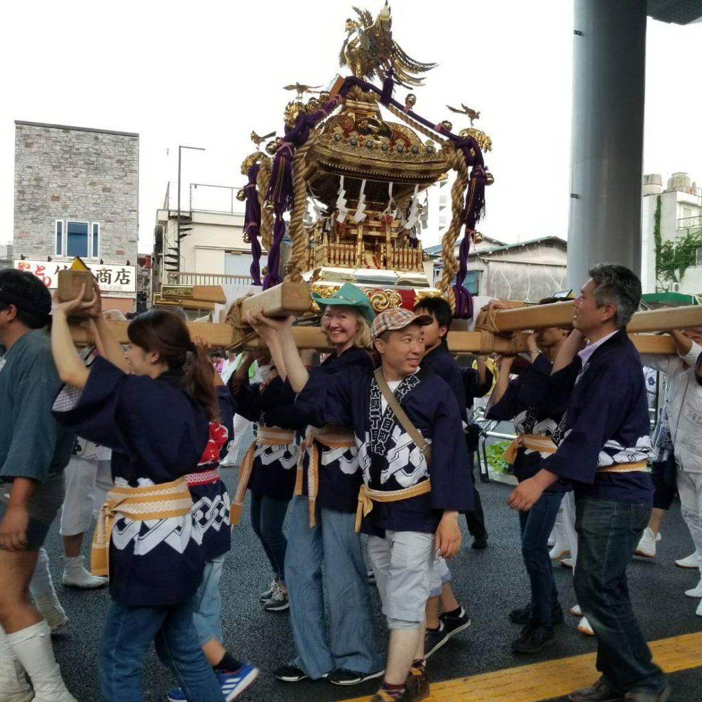 地域のお祭りの模様、神輿を担いでいる、代表の寺田かずとももお神輿の担ぎ手として写っている