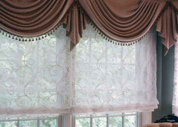 Unlined sheer roman shades underneath Soft swags for bay windows in bedroom