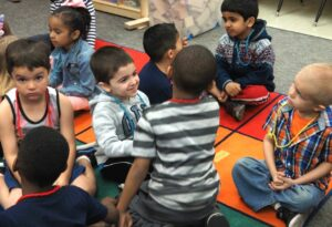 Students in a transitional kindergarten class in Fresno discuss amongst themselves the work of art they just discussed as a class.
