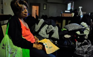 An elderly black woman looking forlorn as she holds an eviction letter in her hands