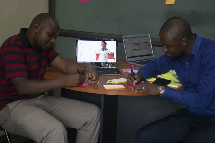 Two Sandbox participants coming up with ideas and writing on post-it notes.